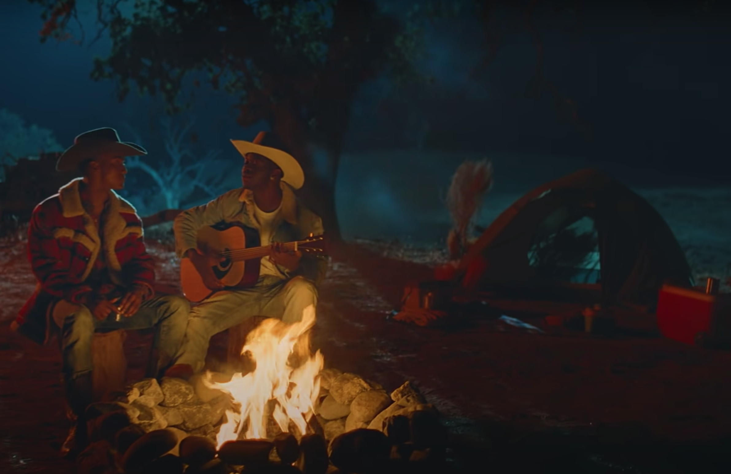 Nas and his lover sitting at a campfire.